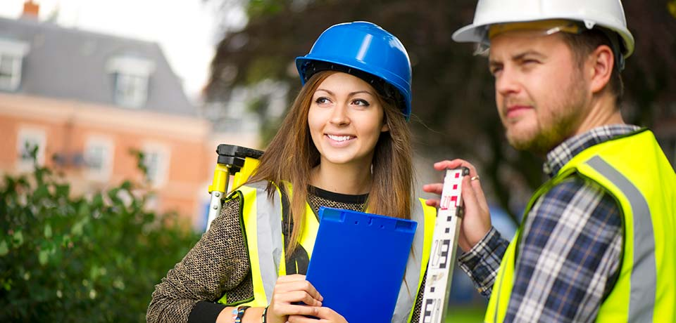 Two people outside wearing hard hats